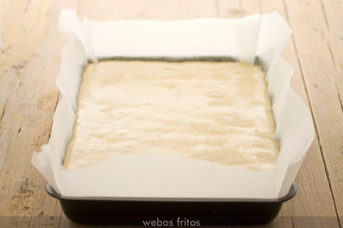 Molde con papel untado de mantequilla y con la masa listo para hornear
